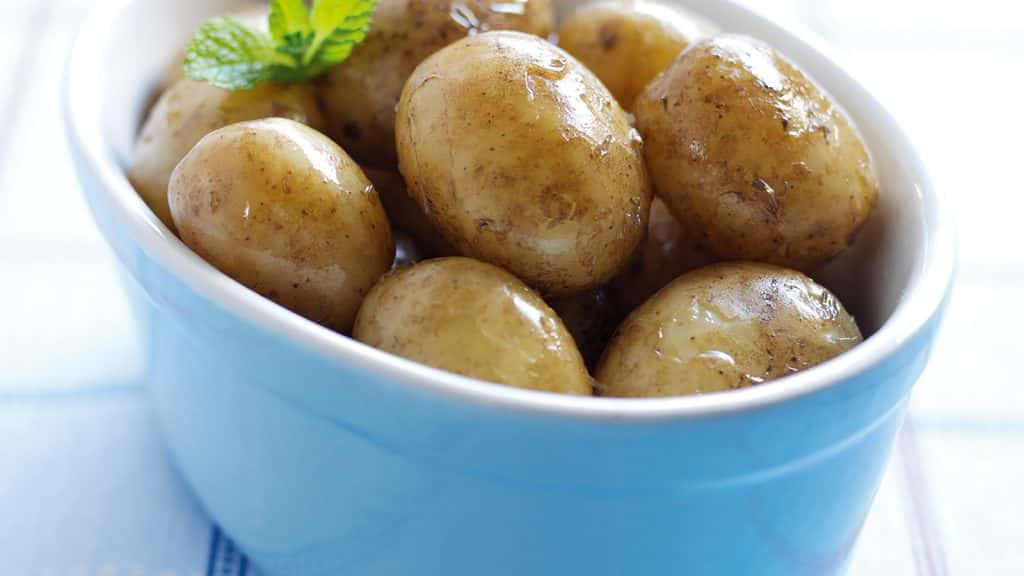 A close-up of a serving dish full of boiled new potatoes
